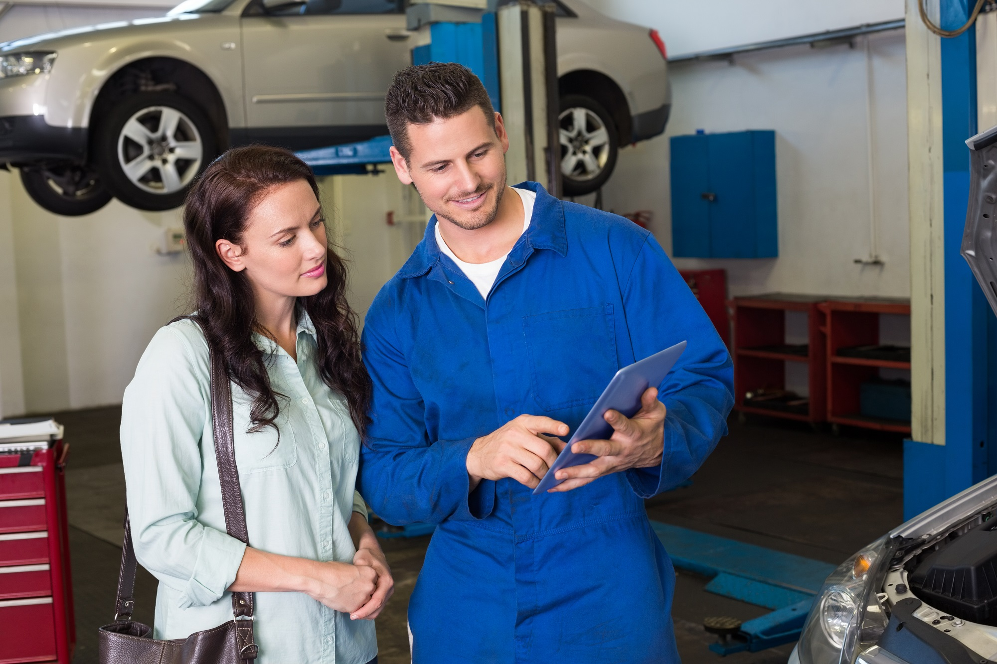Mechanic Showing Tablet Pc To Customer At The Repair Garage
